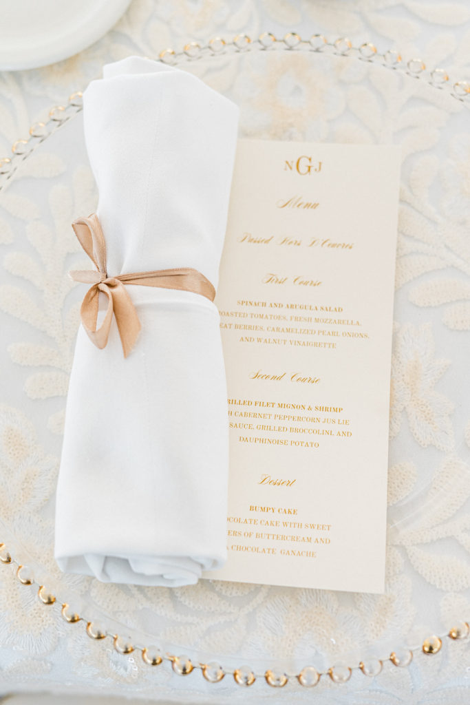 Glass charger with gold rib and folded napkin and menu