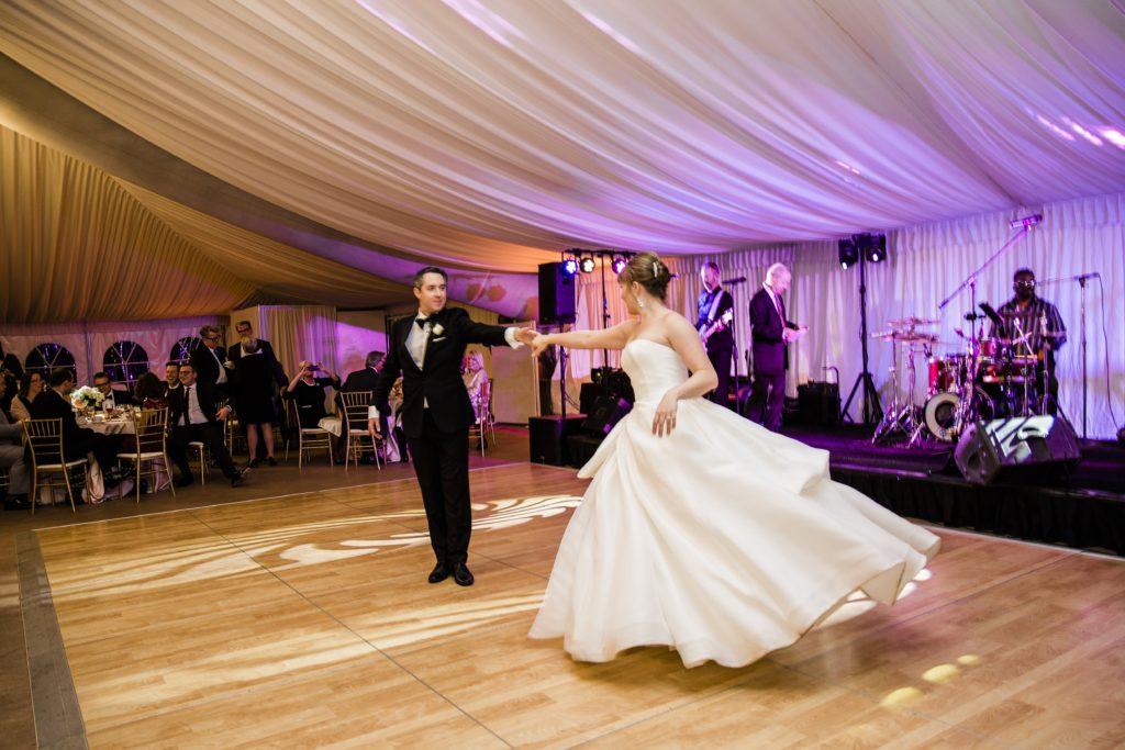 bride and groom on dance floor in tent wedding
